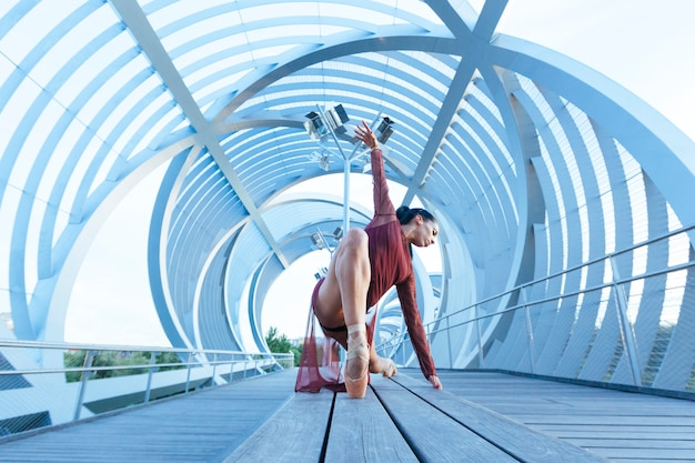 Bailarina, realizando uma pose de balé em uma ponte