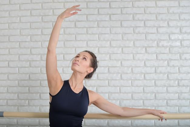 Bailarina se estica perto de barre na sala de aula, mulheres bonitas vestidas com roupa preta praticando balé
