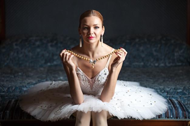 Bailarina sentada na cama segurando um colar de pérolas