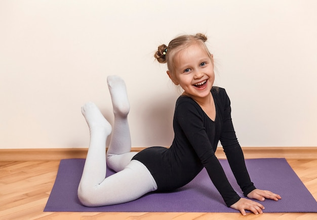 Bailarina sorridente treinando em casa no chão