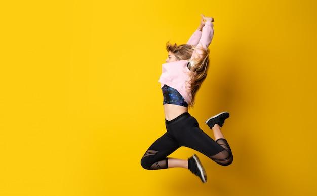 Bailarina urbana dançando sobre fundo amarelo isolado e pulando