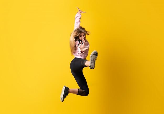 Bailarina urbana dançando sobre parede amarela isolada e pulando