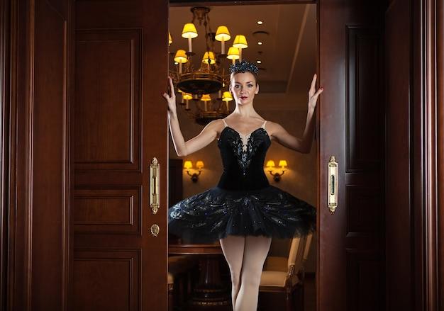 Bailarina vestida de tutu preto em pé na soleira da porta em um interior luxuoso