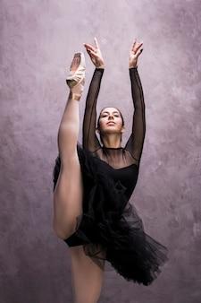 Bailarina vista frontal com uma perna para cima