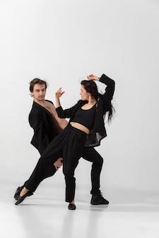 Bailarinos jovens e graciosos em um estilo minimalista de preto, isolados no fundo branco do estúdio