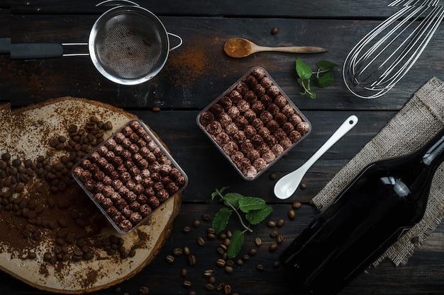 Baileys tiramisu com tampos de bola são apresentados em caixas de vidro. fotografado em um conceito escuro e vintage com decoração de grãos de café.