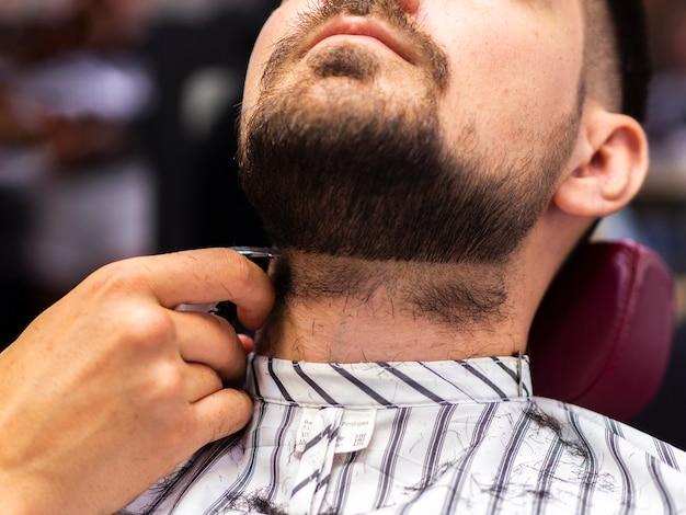 Baixa visão do cliente recebendo seu corte de barba