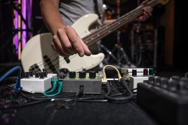 Baixista em um palco com um conjunto de pedais de efeito de distorção.