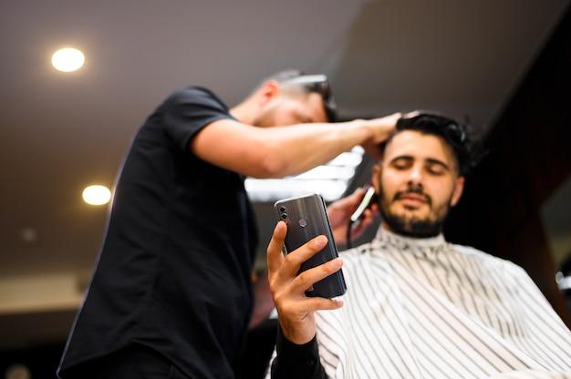 Baixo ângulo, costumer, em, barbeiro, loja, verificar, seu, telefone