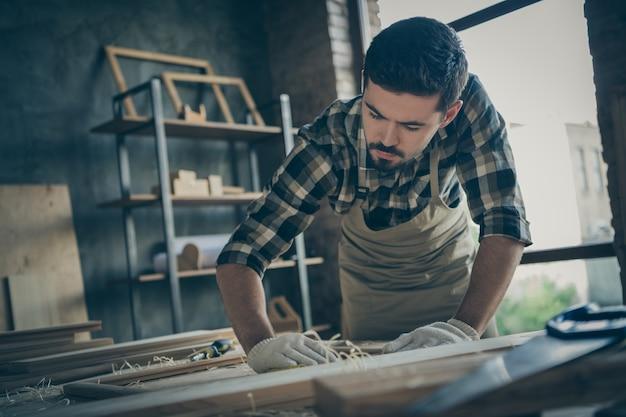 Baixo ângulo de visão sério, confiante, pensativo, homem concentrado focado em polir moldura de madeira com lixa