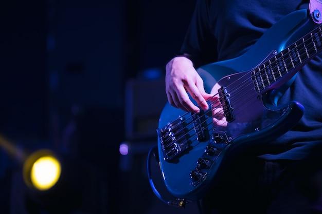 Baixo do guitarrista no palco para plano de fundo, colorido, foco suave e desfoque