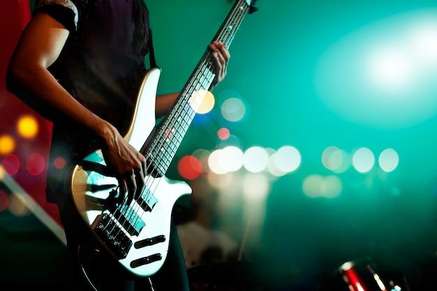Baixo guitarrista no palco para o fundo