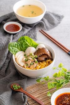 Bak chor mee o macarrão é jogado em vinagre carne picada fatias de porco fígado de porco estufado cogumelos fatiados bolinhos de carne e pedaços de banha frita