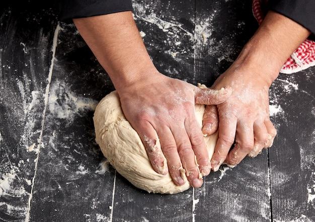 Baker, amassa a massa de farinha de trigo branca sobre uma mesa de madeira preta