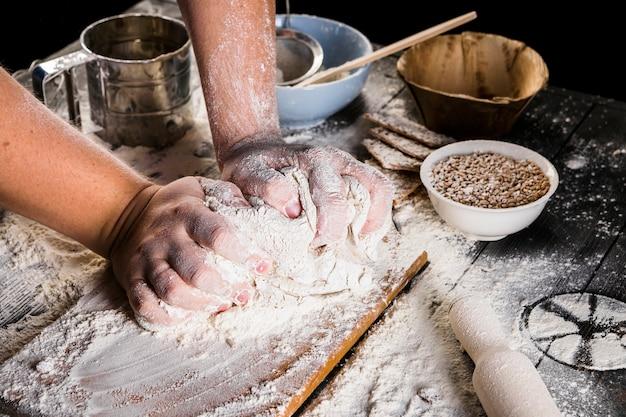 Baker, amassar a massa com farinha sobre a mesa da cozinha