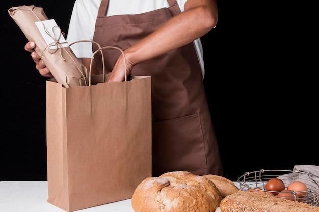 Baker colocando baguete embrulhado em saco de papel