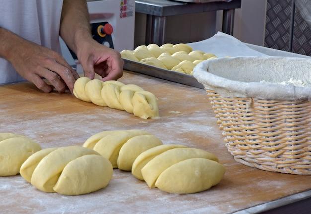 Baker dando forma a pão trançado doce