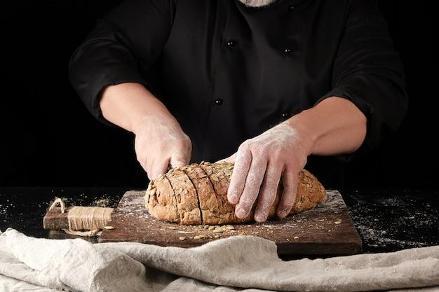 Baker de uniforme preto corta uma faca em fatias de pão de centeio