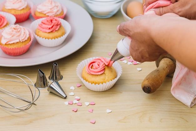 Baker decora muffins com creme sobre a mesa de madeira