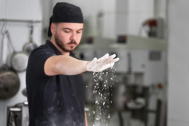 Baker, derramando farinha sobre a massa de pão na cozinha da padaria.