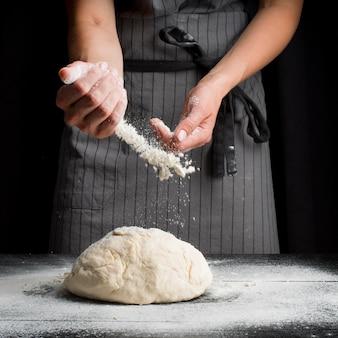 Baker derramando farinha sobre massa