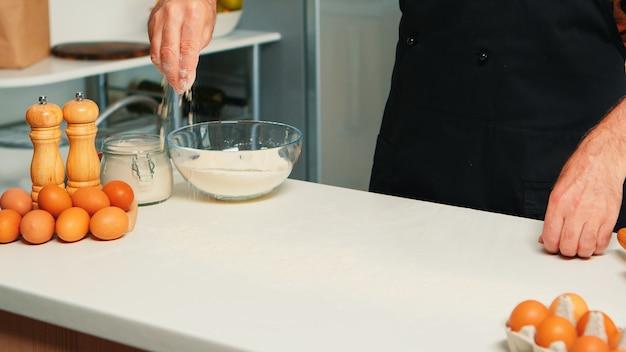 Baker espalhando o ingrediente de biscoitos no tampo da mesa da cozinha. chef sênior aposentado com bonete e avental, em uniforme de cozinha, polvilhando ingredientes peneirados e assando pães e pizzas caseiras