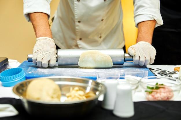 Baker estende a massa sobre uma mesa de cozinha de madeira polvilhada com farinha