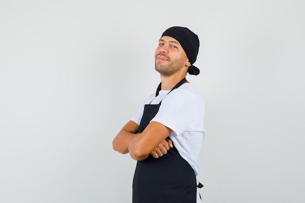 Baker man em t-shirt, avental em pé com os braços cruzados e olhando alegre