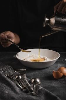 Baker mãos derramando óleo na composição da massa