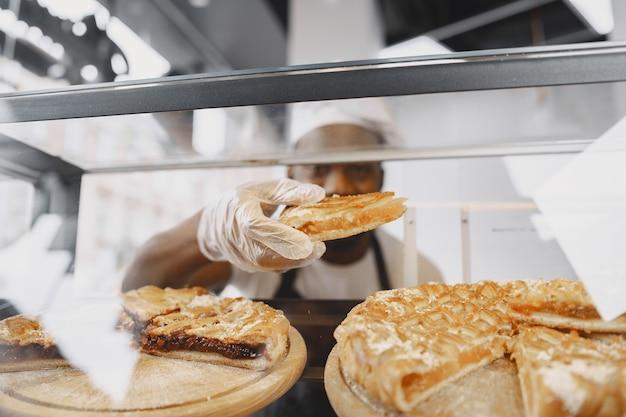 Baker organizando vitrine na padaria. vender produto a um cliente.