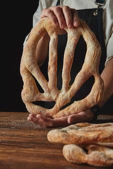 Baker põe pão fougas recém-assado em uma mesa de madeira marrom