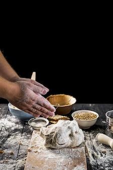 Baker, polvilhando a farinha na massa