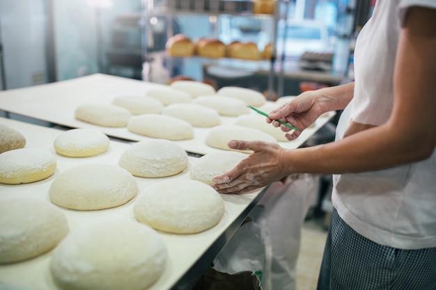 Baker, preparando o pão. feche de mãos amassar massa. conceito de padaria.