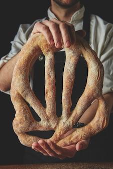 Baker segurando o pão na mão em um close-up de fundo escuro
