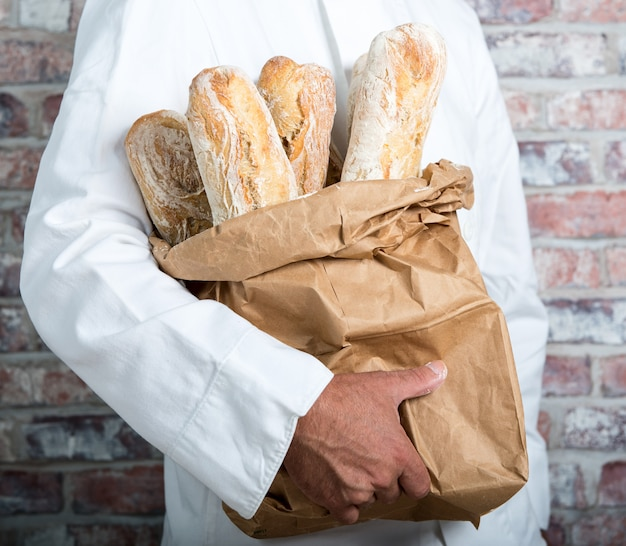 Baker, segurando o pão tradicional francês baguetes