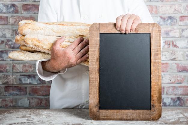 Baker, segurando pão francês baguetes com lousa