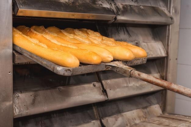 Baker, tirando pão fresco do forno industrial