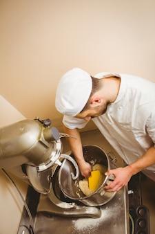 Baker usando o misturador grande para misturar a massa em uma cozinha comercial