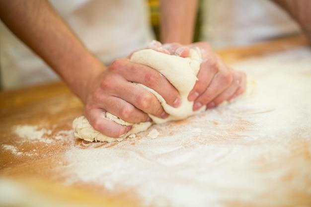 Bakers mãos amassam a massa no contador