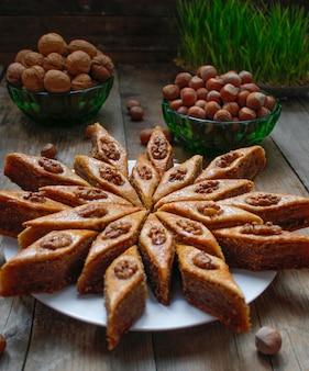 Baklava de cookies de férias tradicional azerbaijão na chapa branca sobre o rústico com nozes