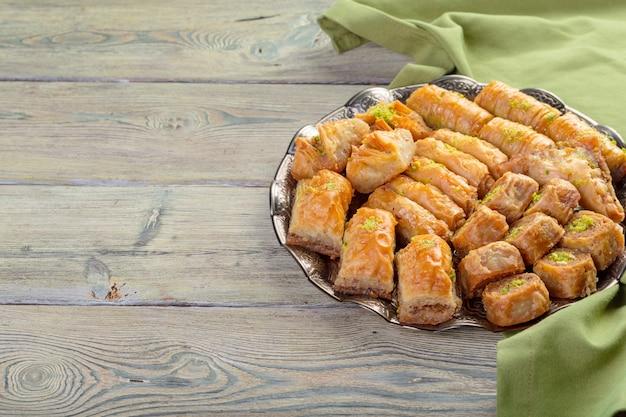 Baklava de doces turcos e bandeja oriental de metal no fundo de madeira