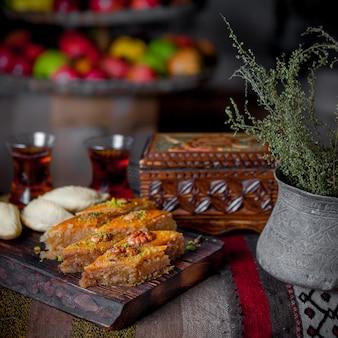 Baklava de vista lateral com shekerbura e caixão e copo de chá na prancha de madeira