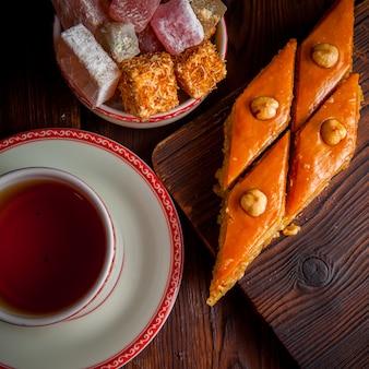 Baklava de vista superior com uma xícara de chá e manjar turco na prancha de madeira