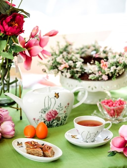 Baklava doce tradicional do azerbaijão com vista lateral e uma xícara de chá com um bule de chá e flores na mesa