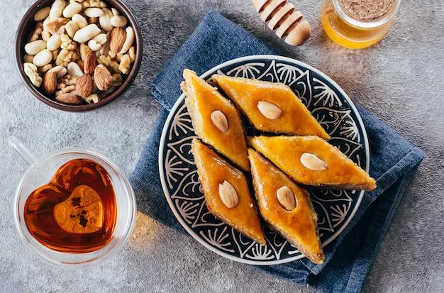 Baklava. sobremesa da ramadã. sobremesa árabe com porcas e mel, copo do chá em um fundo concreto.