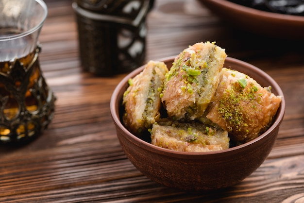 Baklava sobremesa turca com pistache na tigela de barro na mesa de madeira