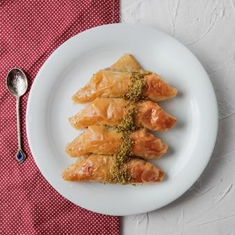 Baklava turco de vista superior com pano e colher em prato redondo