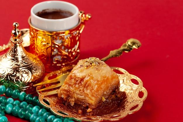 Baklava turco e café em louça oriental sobre fundo vermelho