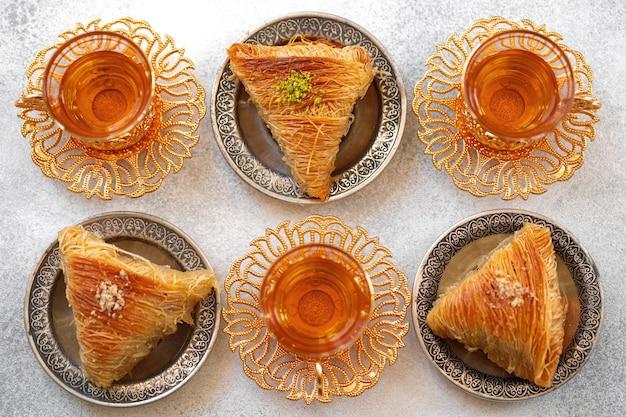 Baklava turco e chá turco em pratos orientais em fundo cinza