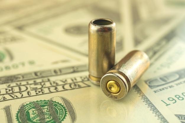 Bala e dólares no fundo, crime e máfia, conceito de dinheiro sangrento, foto de corrupção